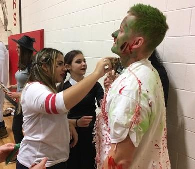 student putting makeup on a teacher