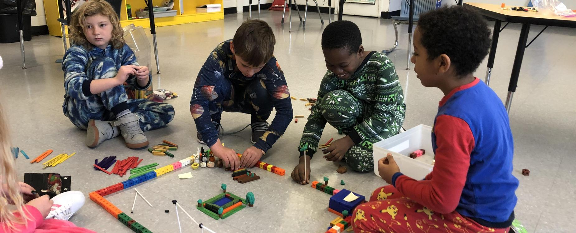 Students are in their pyjamas for Pyjama Day.  5 students are using colored block to build their idea of a community.