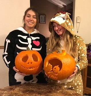 girls in costume holding pumpkins