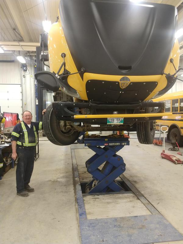 A Sunrise bus in the shop  raised on a lift with a mechanic standing beside the bus for the picture.