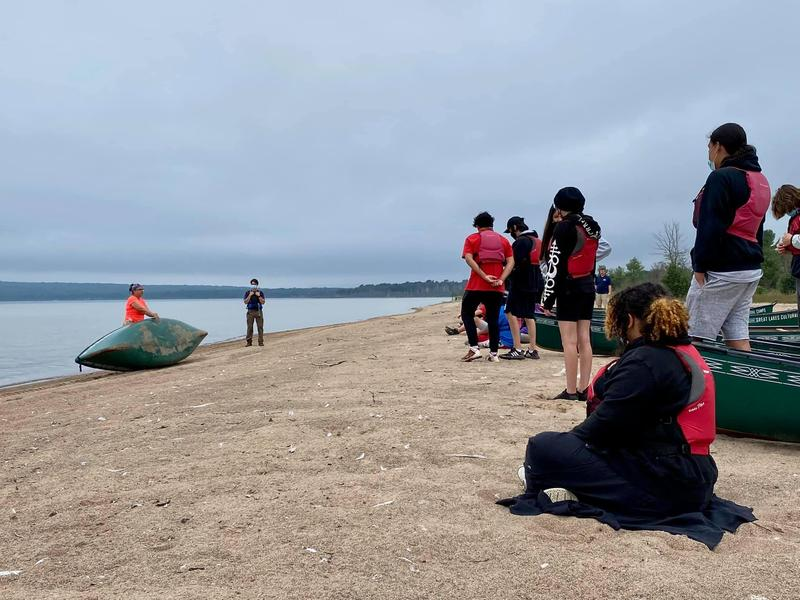 students on beach with teacher and canoes