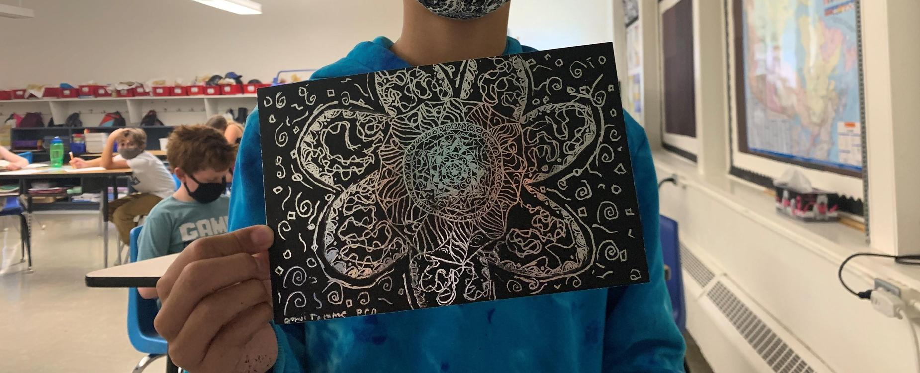 A student is holding up his artwork.  Black picture with with a doodle of a flower etched into the black and swirls around it, showing multiple colors in the etched areas.