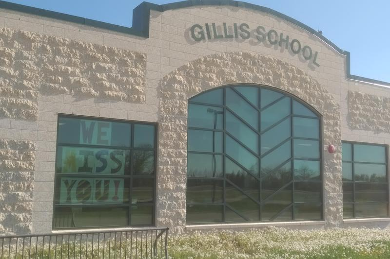 A picture of the front of Gillis School.  It shows 3 large windows a Tyndall stone exterior with the name of Gillis School on the front of the building