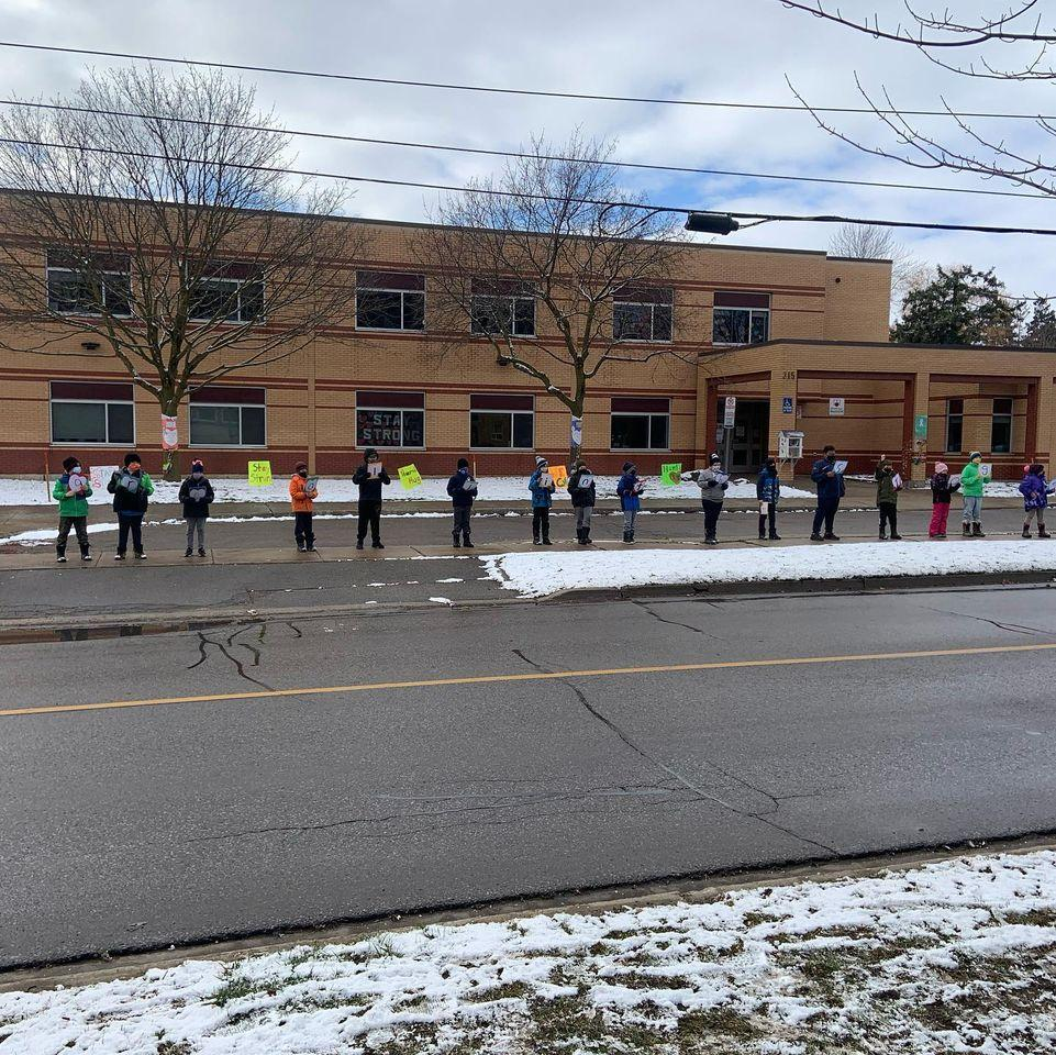 Hamlet PS students standing apart holding signs to support retirement home residents across the street
