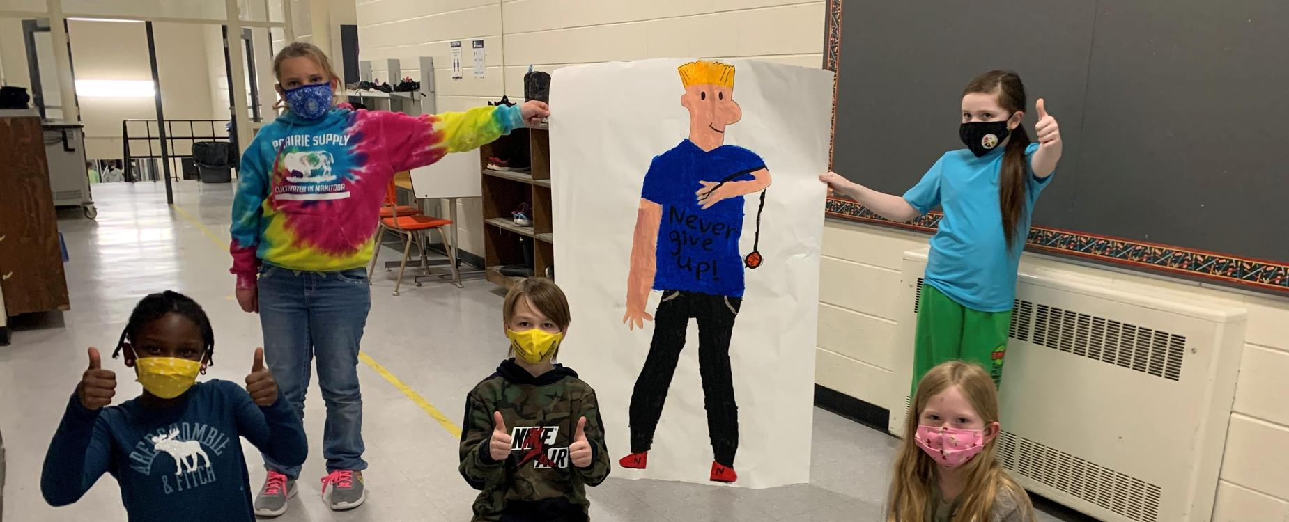 5 students from a Grade 4/5 class, posing in the hallway with 2 students holding a life-sized picture of the NED character.