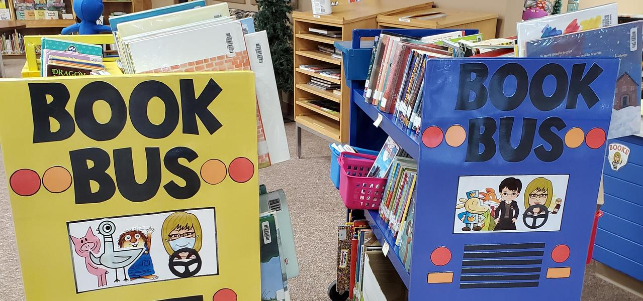 Two rolling carts, decorated as school buses, one blue and one yellow, titled Book Bus.  Each cart was filled with books for students to read.