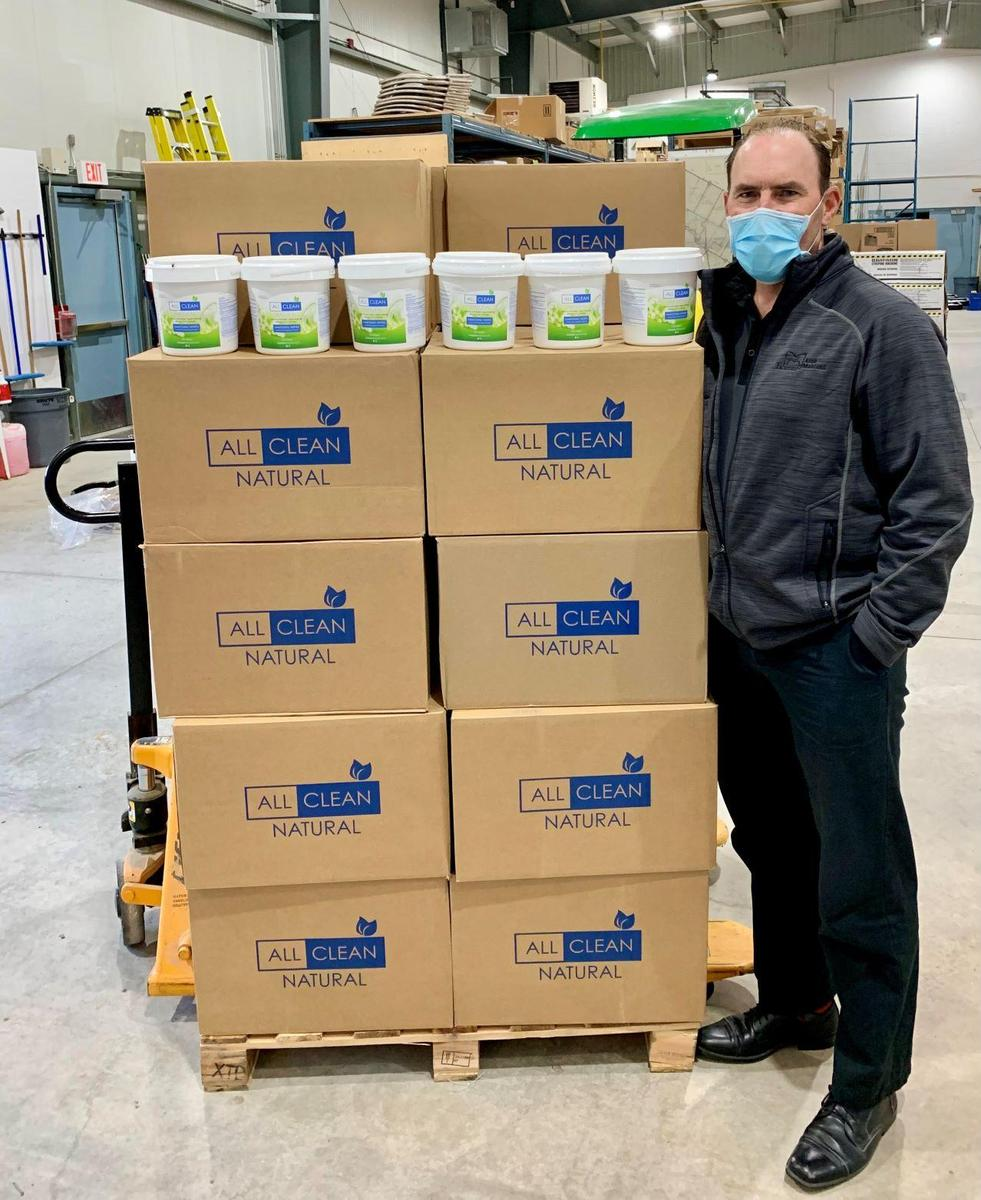 Photo of staff member standing beside skid filled with buckets of technology cleaning wipes