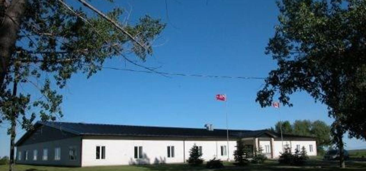 A picture of Springwell School.  The building is white and the roof black. Trees surround the school grounds.