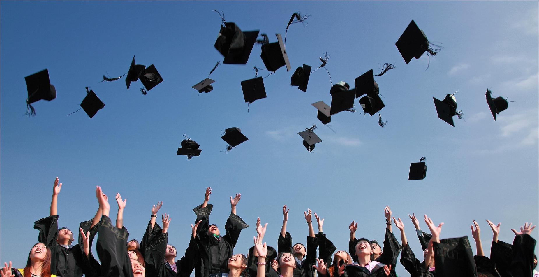 Students throwing hats in the air