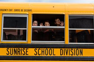 A side view of a bus that reads Sunrise School Division and 3 students waiving out one window.