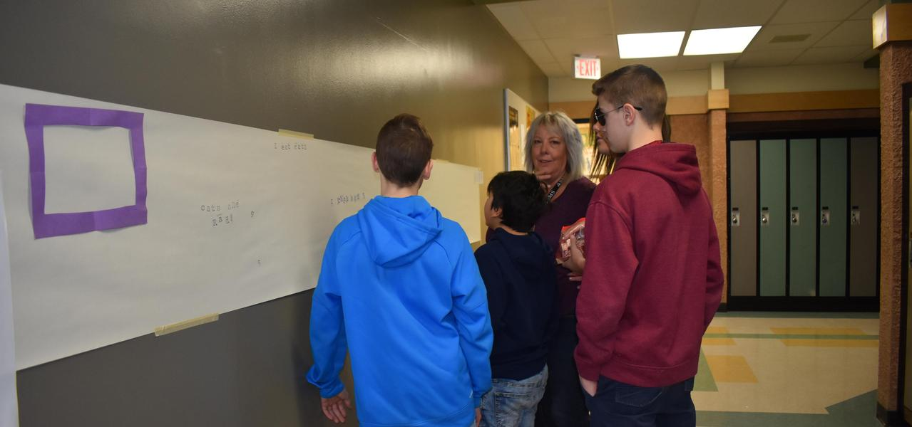Students and a teacher working together.