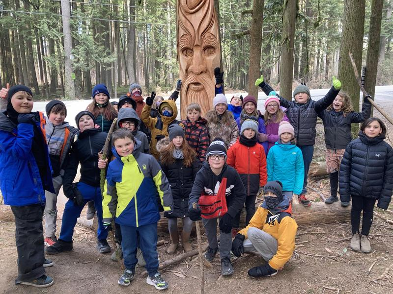 students in front of carving