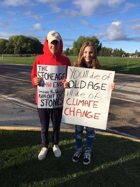 Two students standing with signs in support of Climate change strike