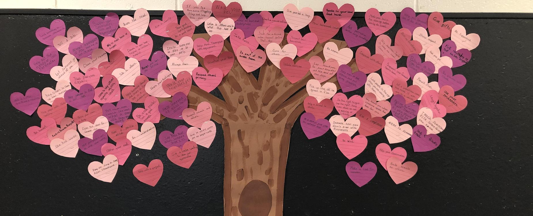 A billboard decorated with a brown tree and pink hearts as leaves.  There are 100 hearts with acts of kindness written on them.  The list is compiled by Mme. Knutson's grade 4/5 class.
