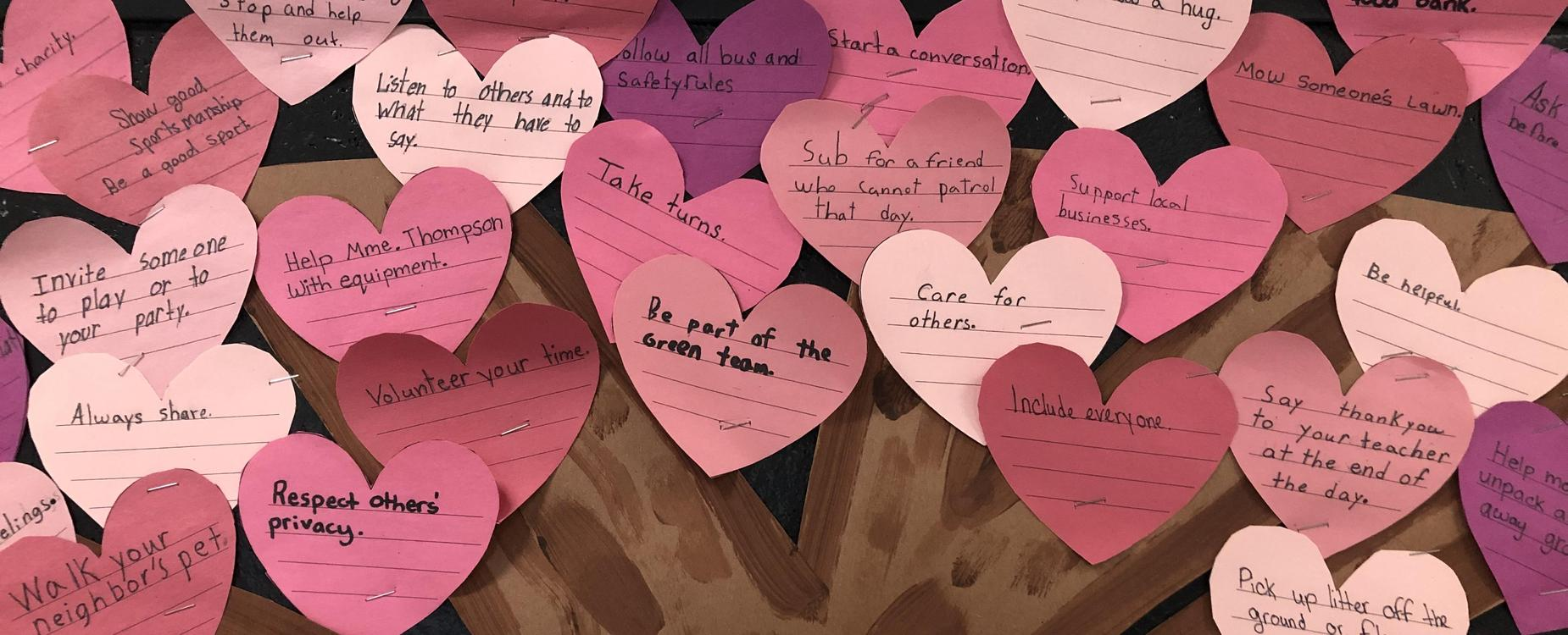 A closer look at a billboard with pink heart-shaped leaves on a tree that list acts of kindness, by the students in Mme. Knutson's Grade 4/5 class.