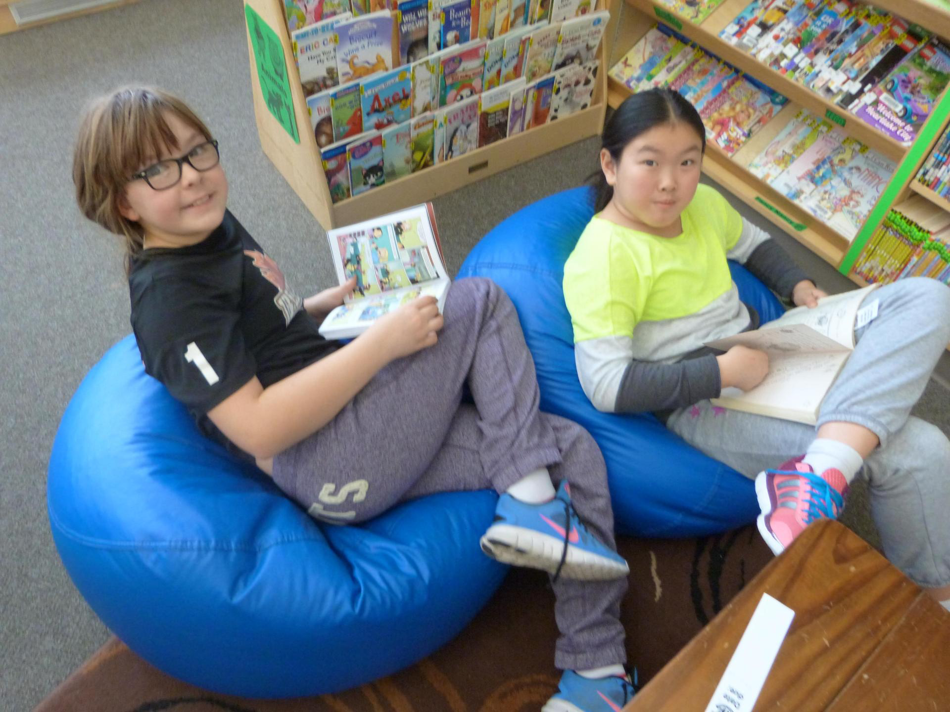 two students reading in bean bag chairs