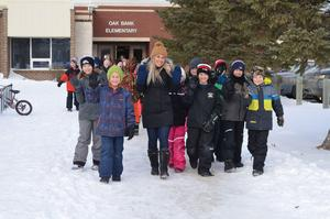A group of students and a teacher walking outside of the school in a winter setting.