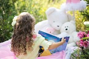 girl reading book to stuffed animals