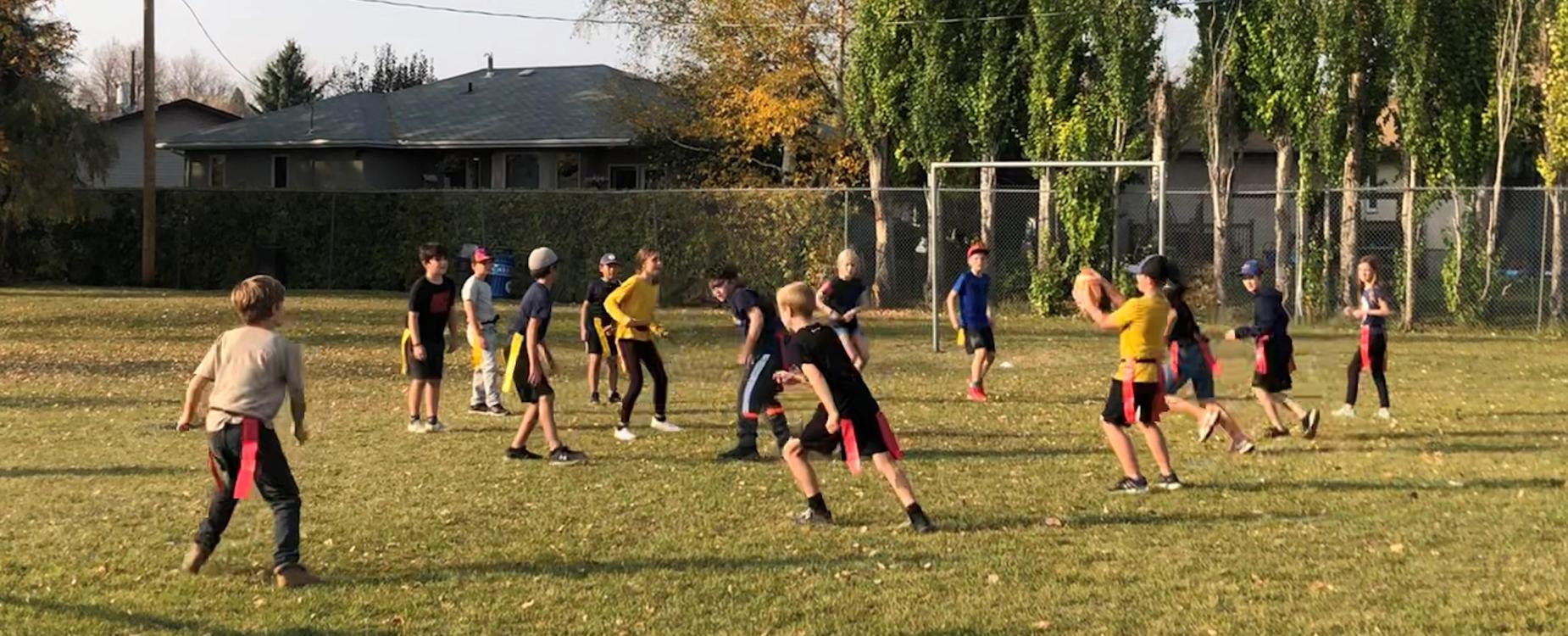 Grade 4/5 students are playing a flag football game.  The ball has just been tossed to the quarterback, and team is on the run.