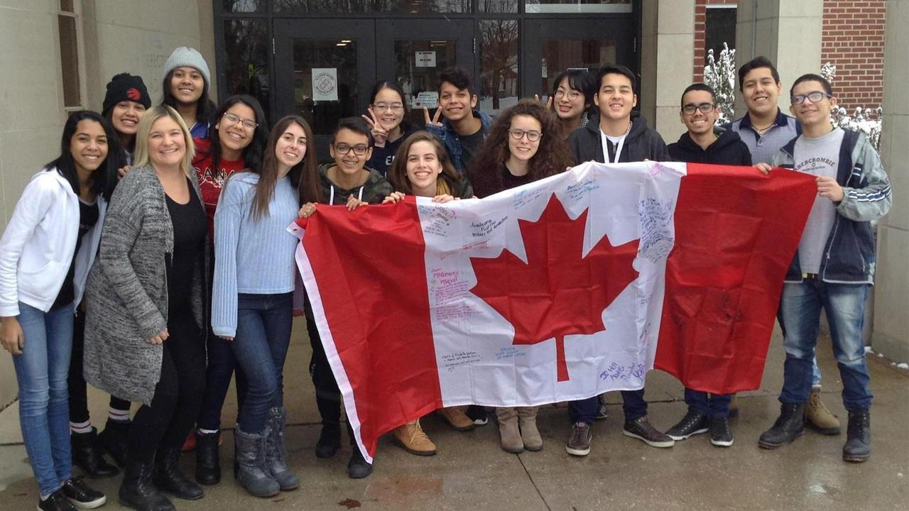 Group of students smiling at the camera while holding a large Canadian flag