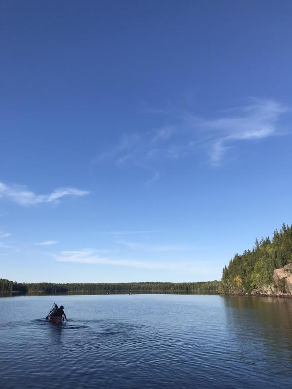A beautiful lake view of the water with surrounding trees and a canoe in the water.