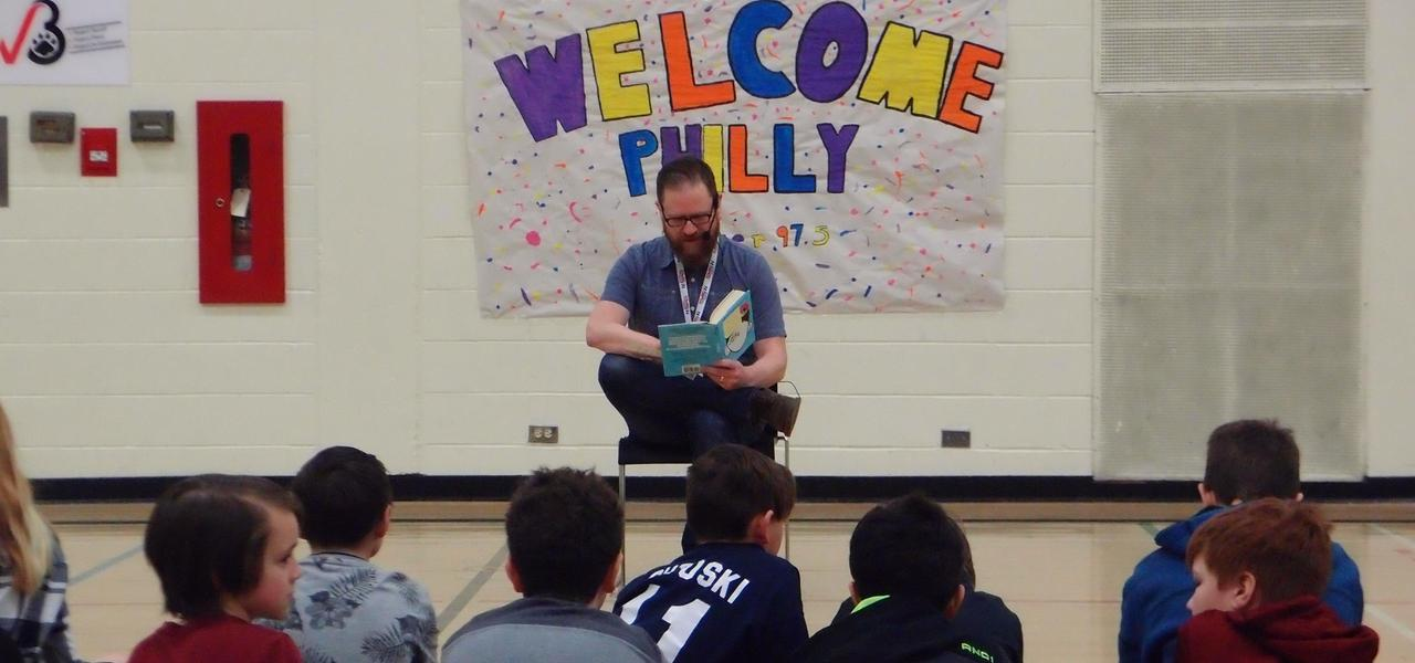 A man reading a book to a group of students in the gymnasium.