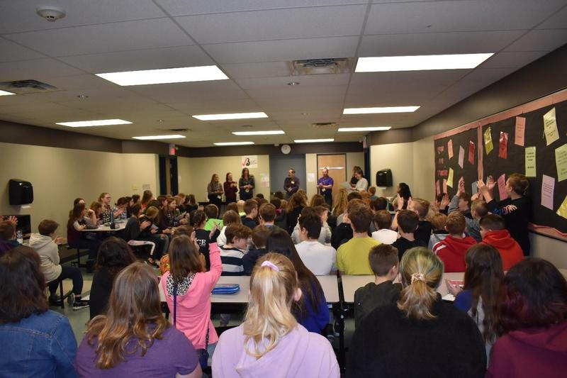 A classroom filled with students and adults.  A group of adults presenting at the front of the classroom. Many students have their hands up to ask questions.