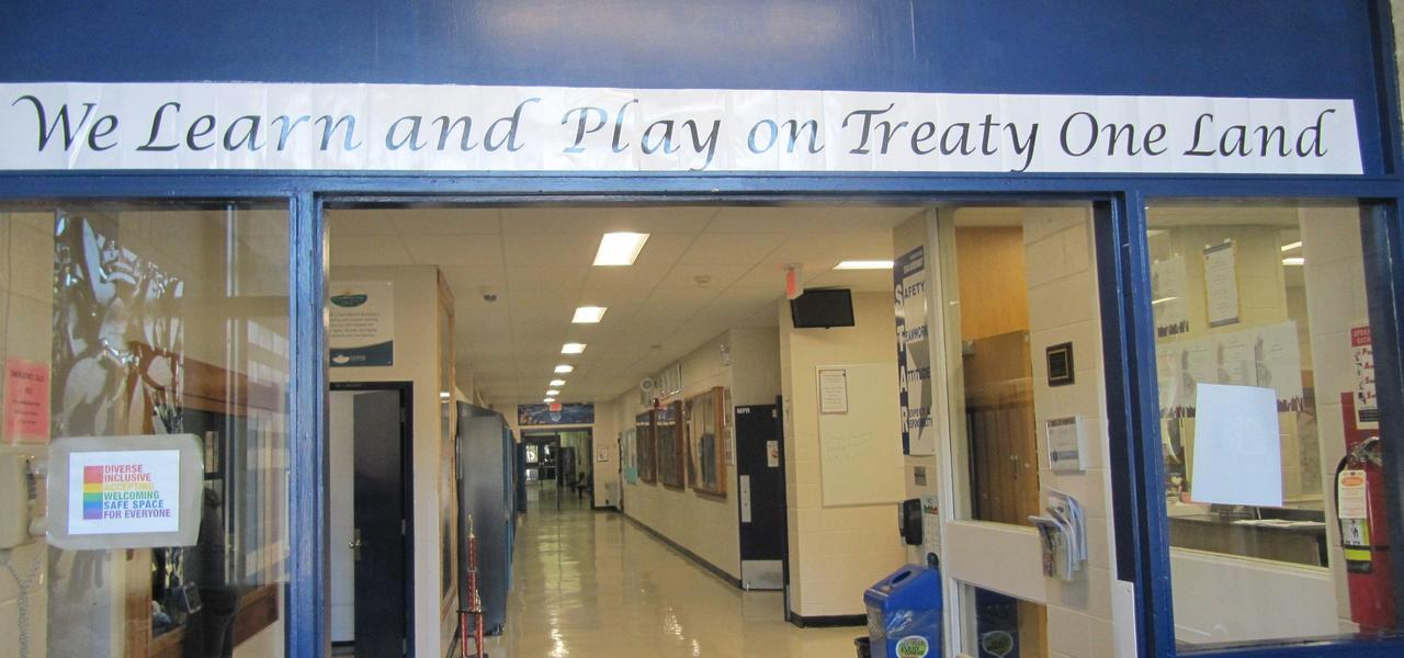 We Learn and Play on Treaty One Land banner in school entrance.
