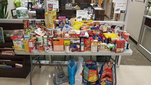 A table full of food, consisting of can good, cereal, pasta baby food and many other items that are being donated to the food bank.