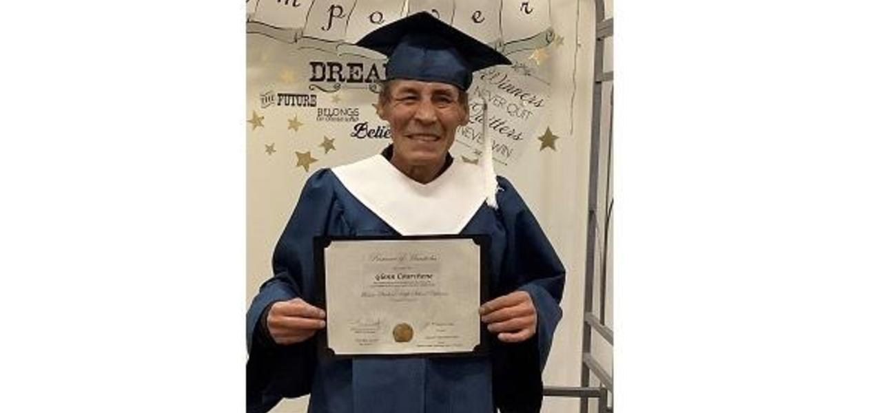 mature graduate holding grade 12 diploma.  He is wearing a blue cap and gown.