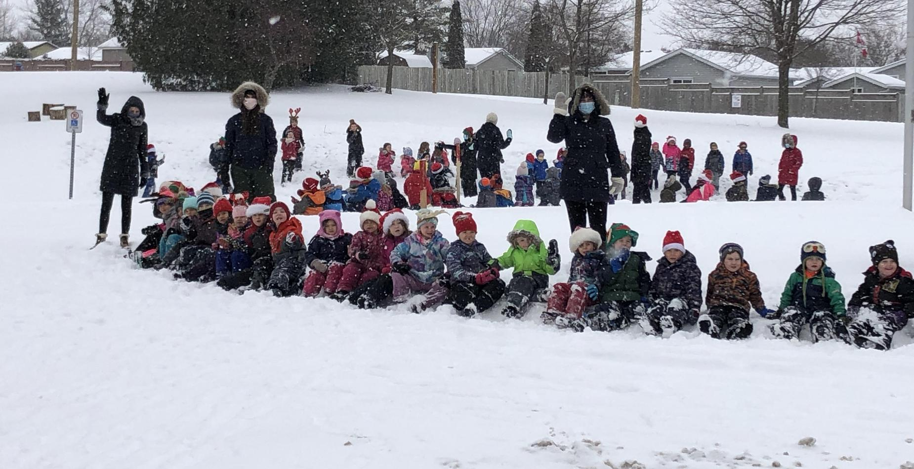 Primary students sitting in snow watching Christmas Parade