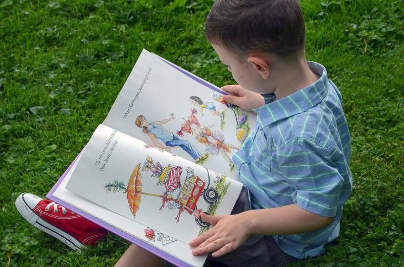 young boy reading on grass