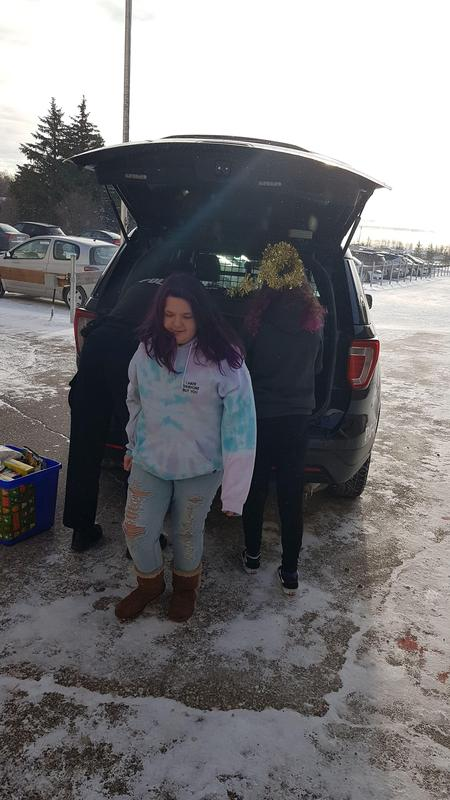 A van is being loaded with food by a couple of students.