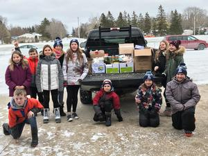 Social Justice kids posing with food for the Food Bank.