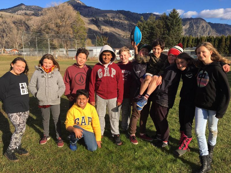 Elementary students ready to play touch football in the fall sunlight