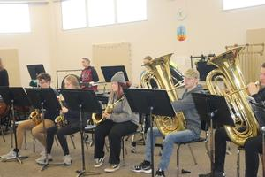 Student sitting in a row playing instruments.  Wind instruments are in the front row.