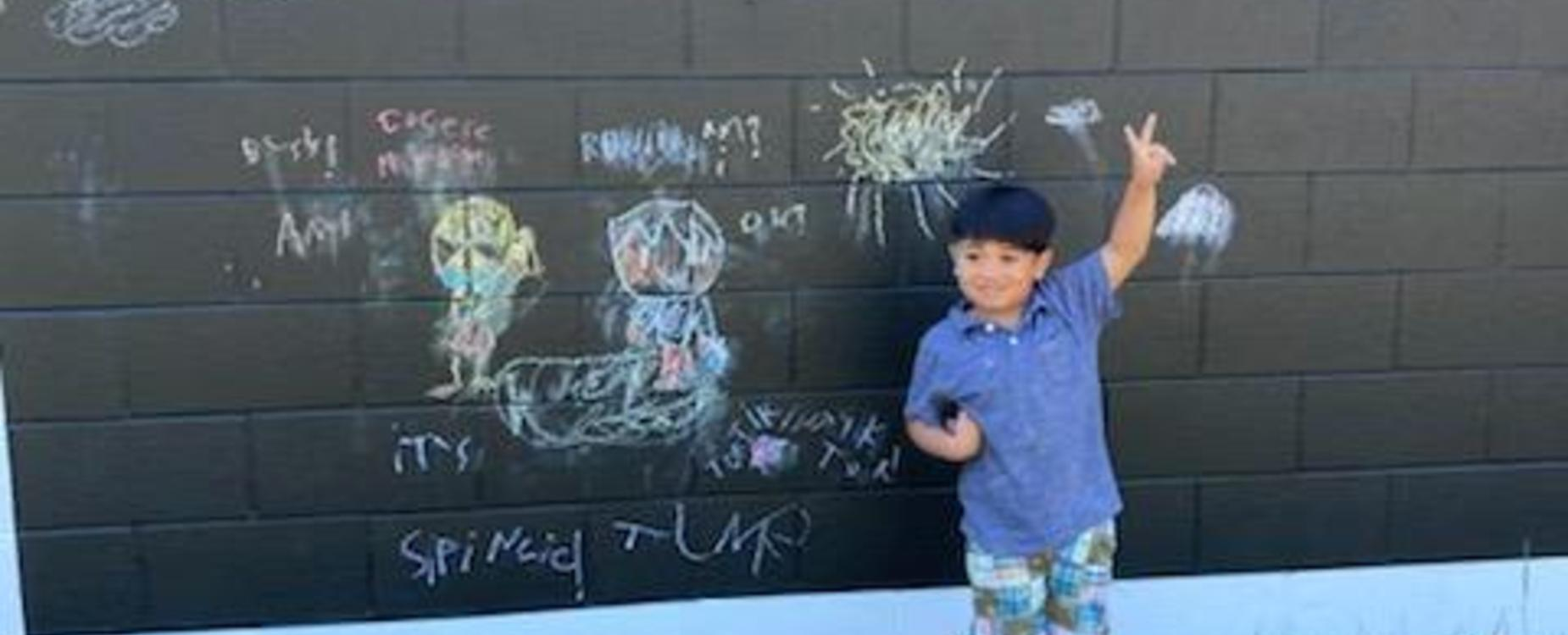 A student posing in front of his drawing on the new outdoor chalkboard paint walls.