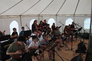 Students playing ukulele on stage.