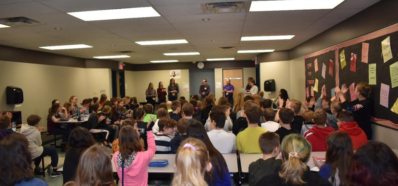 A large group of people including students and adults in a classroom.  A group of adults at the front of the room presenting.  Many students have their hand up to ask questions.