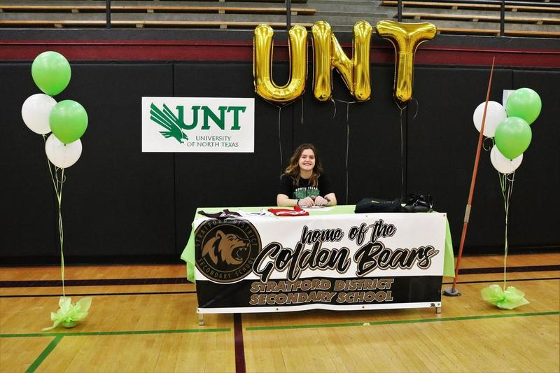 Female student sitting at a table decorated with SDSS and University of North Texas gear
