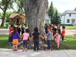 Children holding hands in a circle around a large tree