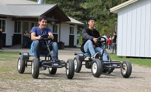 two boys racing pedal cars