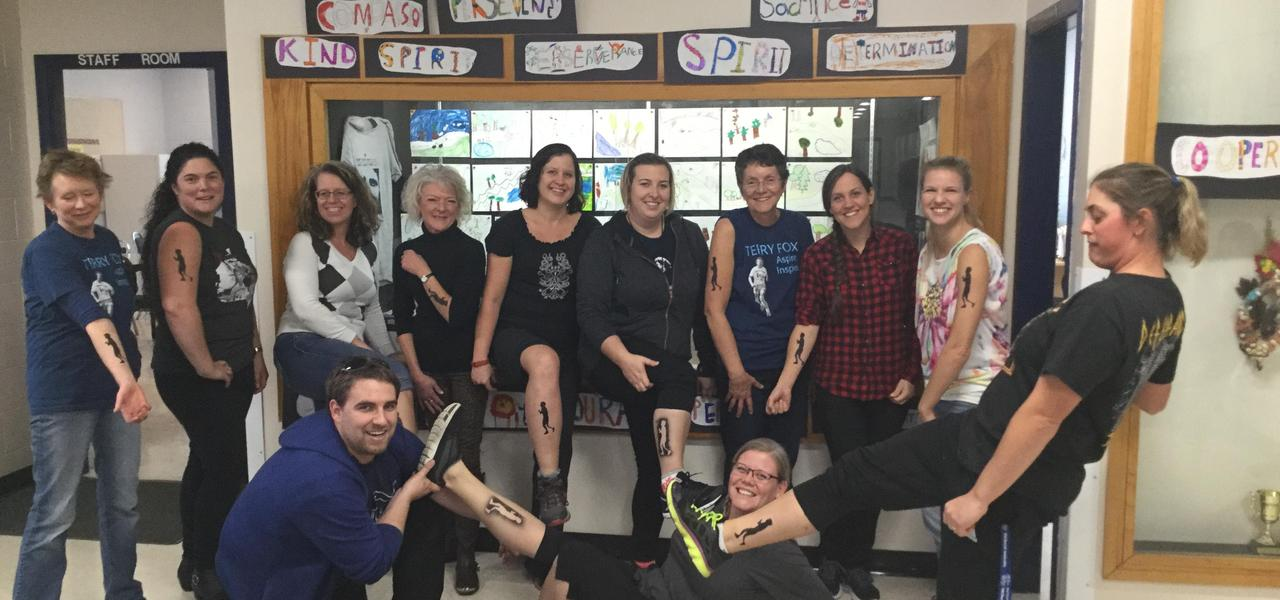 female staff posing with their Terry Fox tattoos