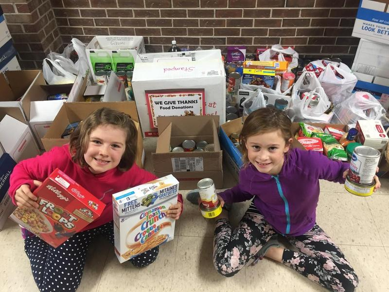 Smiling students in front of donated canned goods for