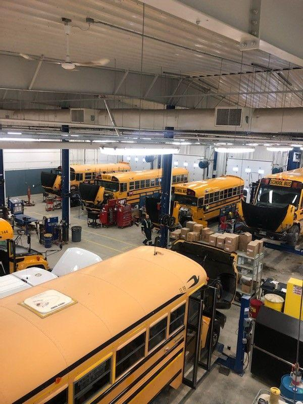 The Sunrise Bus shop with 6 buses inside being worked on by the mechanics.
