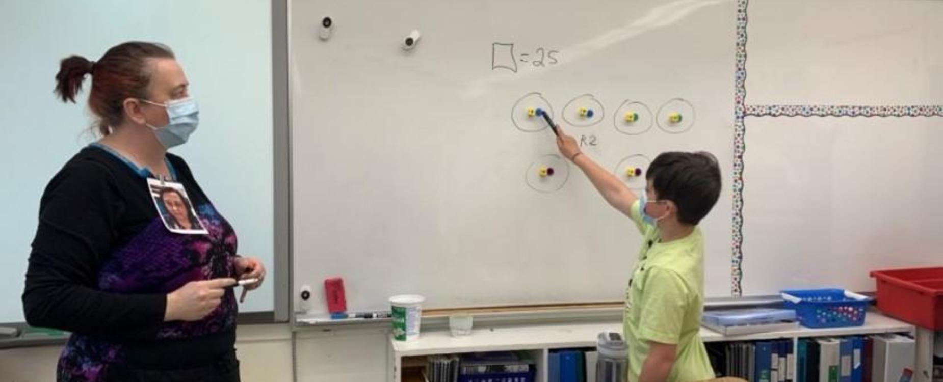 Teacher watching a student working through a math problem on the whiteboard.