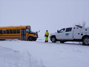 Sunrise service truck assisting a Sunrise Bus that has slid slightly off the road.