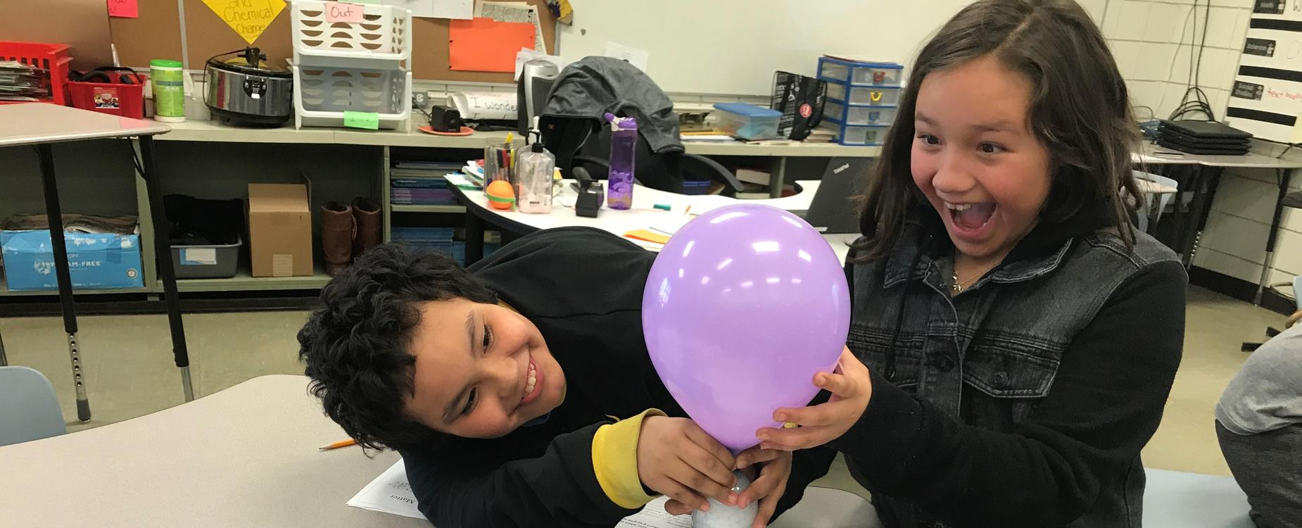 2 students do a science experiment with a balloon and water bottle