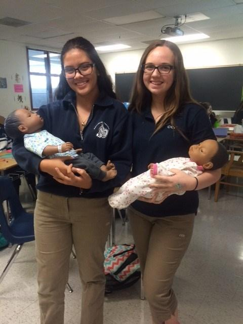 Two female students holding baby dolls