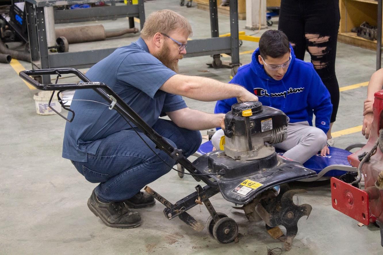 student and teacher working on a tiller
